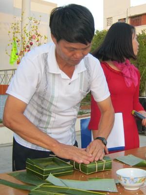 Ông Đồng Xuân Trường, cán bộ hưu trí của trường trong vai trò hướng dẫn gói bánh cho các sinh viên.