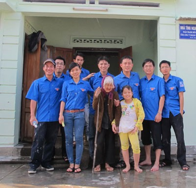 Đoàn viên, thanh niên Tổng Công ty Khánh Việt và mẹ Võ Thị Hộ bên căn nhà vừa được sơn mới.