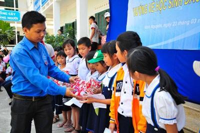 Ban tổ chức trao quà cho các học sinh nghèo vượt khó.