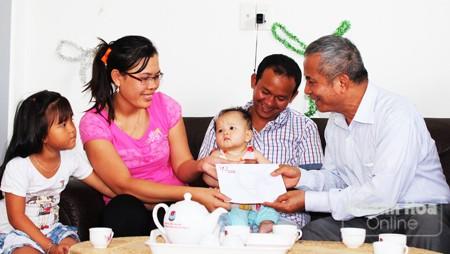 Ông Đặng Ngọc Tùng (bìa phải) thăm, tặng quà gia đình chị Trần Thị Thủy