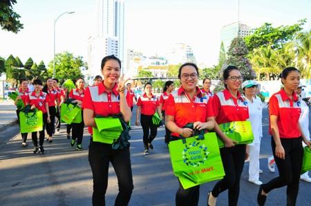 Các nhân viên Lotte Mart mang theo túi  thân thiện môi trường để phát cho người dân.