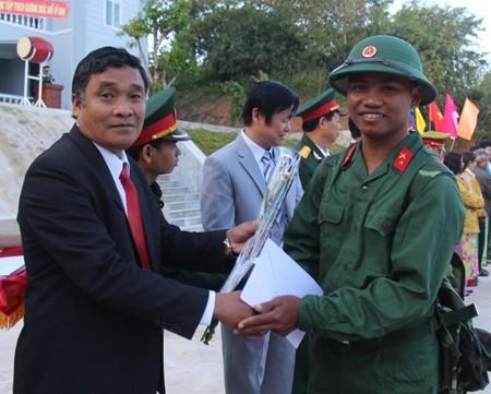 Ông Mấu Thái Cư - Bí thư huyện ủy Khánh Sơn tặng hoa cho các thanh niên địa phương lên đường nhập ngũ.