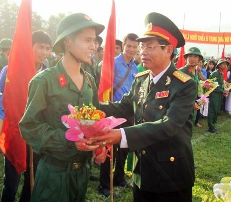 Đại tá Trần Thân - Phó Chính ủy Bộ Chỉ huy Quân sự tỉnh Khánh Hòa tặng hoa động viên các tân binh.