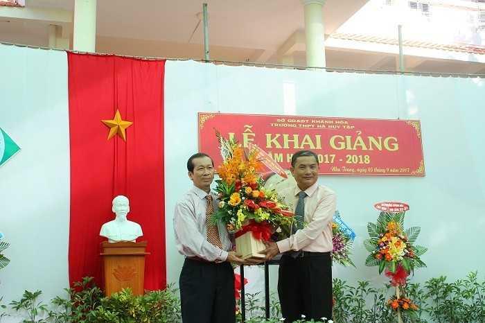 Ông Nguyễn Chuyện (bên trái) tặng hoa chúc mừng khai giảng cho lãnh đạo Trường THPT Hà Huy Tập