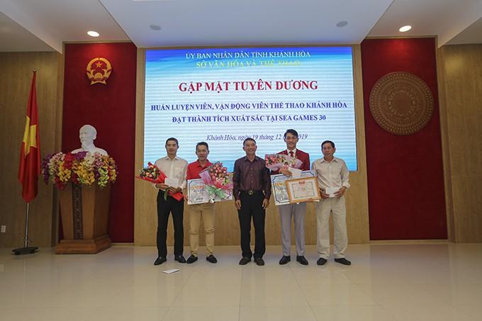 Ông Trần Quang Thưởng tặng thưởng cho 2 HLV đội tuyển điền kinh tỉnh Lê Đình Hải (trái), Ngô Văn Phúc (phải) vì có công trong việc tìm kiếm đào tạo VĐV đạt thành tích cao.