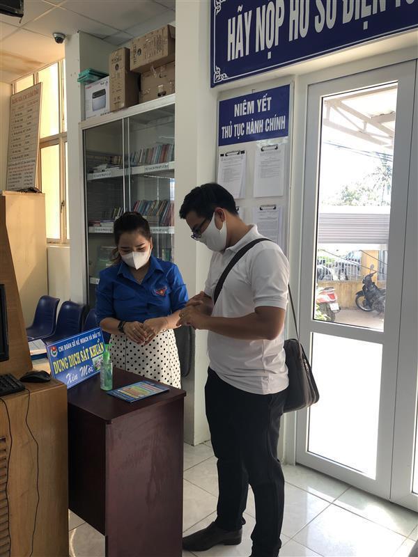 Phát khẩu trang và tờ rơi tuyên truyền phòng, chống dịch Covid-19 cho người dân đến liên hệ công việc tại Bộ phận một cửa